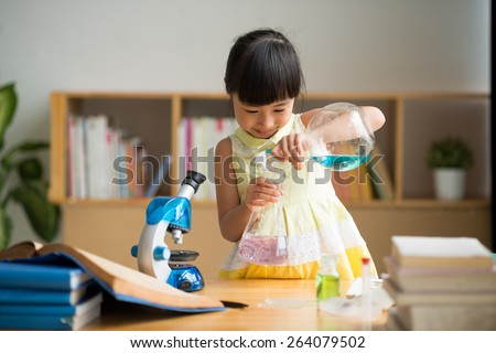 Curious Vietnamese girl pouring reagent into flask - stock photo
