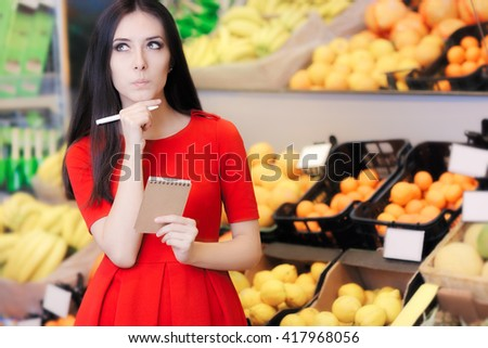 Curious Woman in The Supermarket with Hopping List - Young girl in a market store with a shopping list thinking what to buy   - stock photo