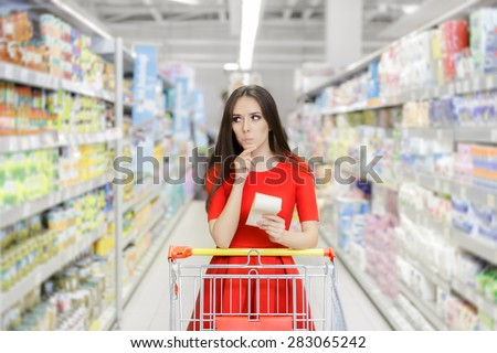 Curious Woman in The Supermarket with Shopping List- Young girl in a market store with a shopping list thinking what to buy  - stock photo