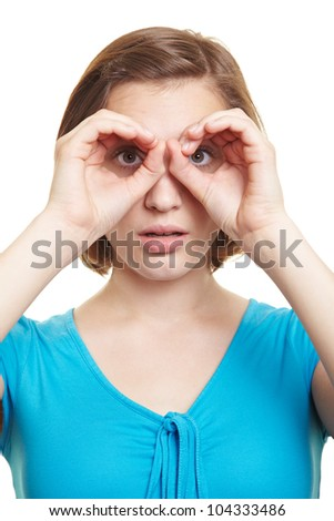 Curious woman looking through her fingers in front of her eyes - stock photo