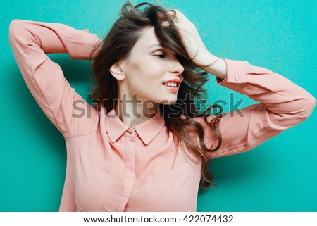 Curious Woman. Young woman in pink shirt on blue background. - stock photo