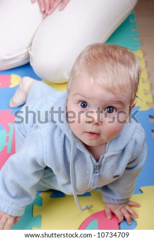 Curious young boy lying on floor in background his mother