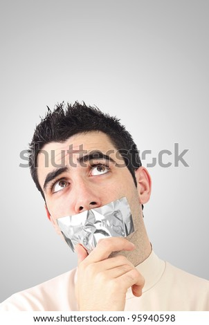 Curious young man having gray duct tape on his mouth.Gradient background with copy space.