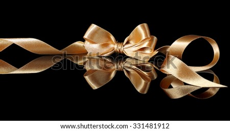 Curled golden ribbon with bow on a black background - stock photo