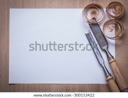 Curled wooden shavings firmer chisels and blank sheet of paper on wood board copyspace image construction concept.