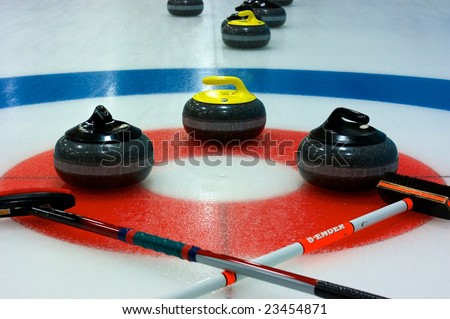 Curling rocks and brooms laid out around the button
