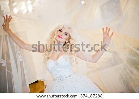 Curly blonde bride  posing on curtains