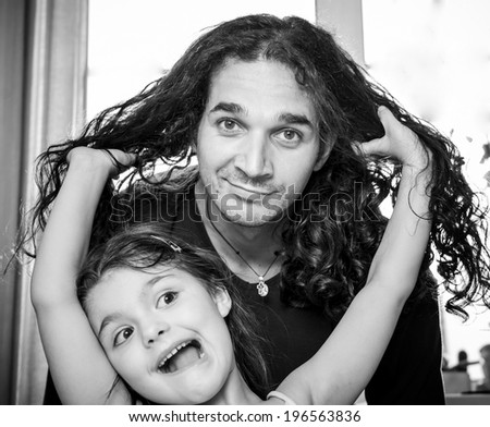 Curly dad plays with daughter. - stock photo