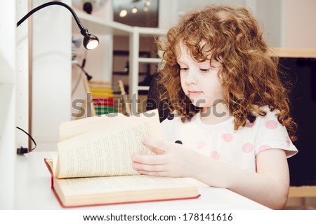 Curly girl reading a book at his desk. - stock photo