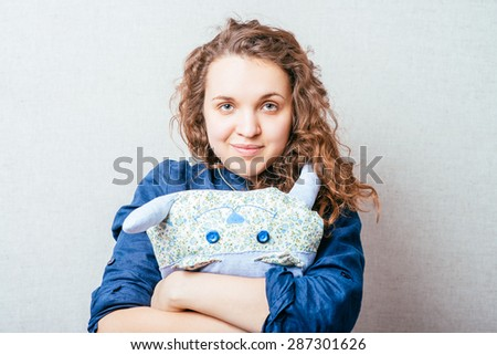 Curly girl toy cat pillow. Gray background. - stock photo