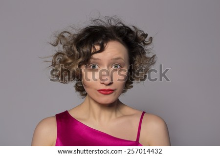 curly girl with short hair looking into the camera. studio shot - stock photo