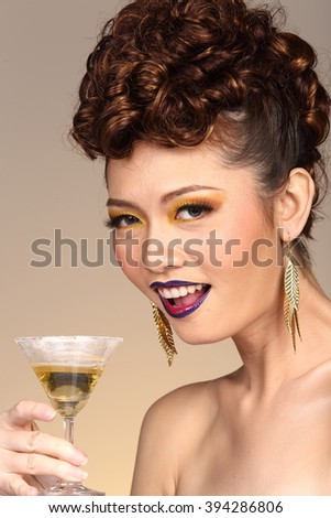 Curly Hair Asian Female Model with Fashion Make Up holding Cocktail glass with gold ear rings in Studio Lighting