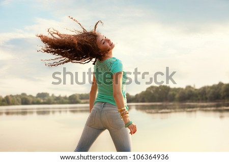 curly hair young woman jump in front of lake  summer day casual clothes