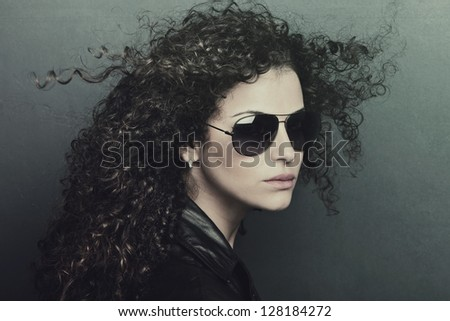 curly hair  young woman with sunglasses studio shot - stock photo
