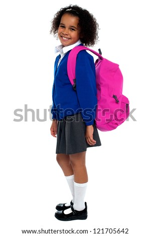 Curly haired elementary school girl carrying pink backpack on shoulders. - stock photo