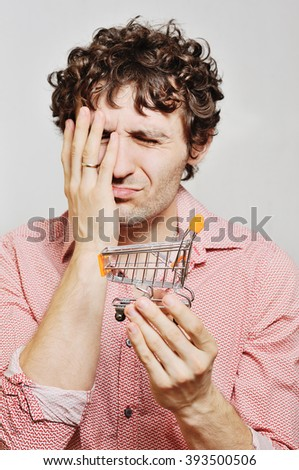 curly-haired guy with a small trolley for a supermarket in their hands. Financial constraints, rising prices, low wages. - stock photo
