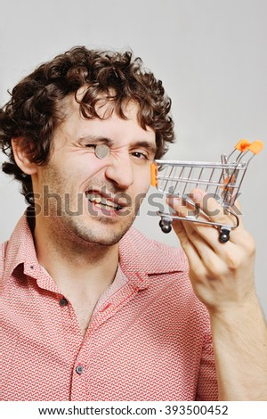 curly-haired guy with a small truck to a supermarket and a coin in the eye. Financial constraints, rising prices, low wages. - stock photo