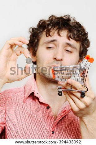 curly-haired guy with the Russian ruble and the small cart from the supermarket in your hands. Financial constraints, rising prices, low wages. - stock photo