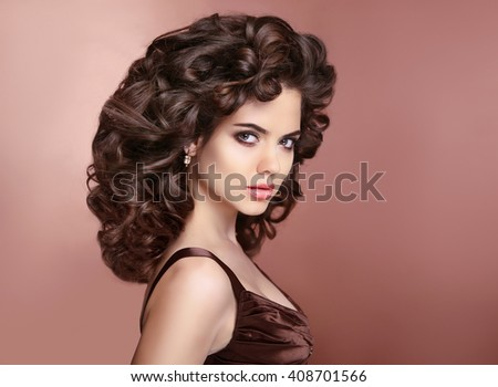 Curly hairstyle. Attractive brunette girl with makeup. Brunette. Expressive eyes stare. Elegant lady over studio beige background. Luxury vogue style - stock photo