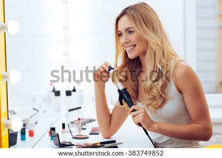 Curly is better! Side view of beautiful young woman looking at her reflection in mirrorand using her curling iron while sitting at the dressing table - stock photo