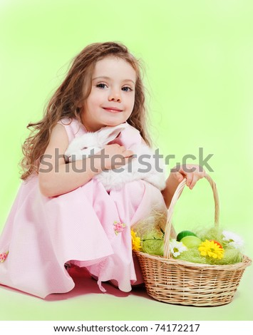 Curly little girl with Easter basket and white bunny in hands - stock photo