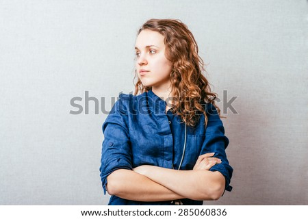 Curly woman folded her arms. On a gray background. - stock photo