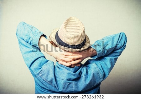 Curly young man in a wicker hat over his head put his hands resting. Back view. On a gray background - stock photo