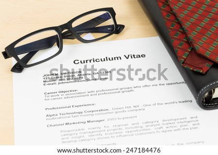 Curriculum vitae or CV with glasses, organizer, and neck tie; concept job applying - stock photo