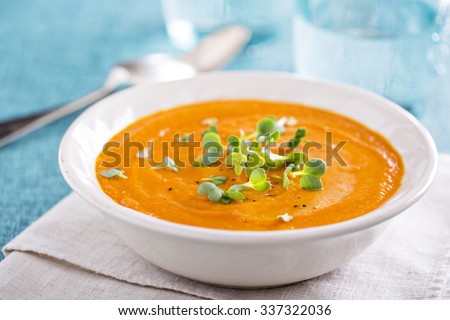 Curried carrot soup with cream and fresh herbs - stock photo