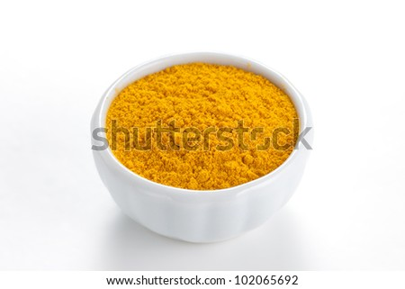 Curry ground (Madras Curry) in a white bowl on white background. Used as a spice in cuisines all over the world. - stock photo
