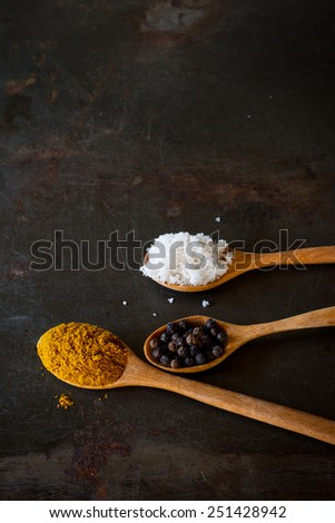 curry powder and pepper heap in wood spoon soft focus , put on grunge metal background - stock photo