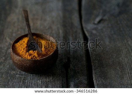 curry powder on wooden surface - stock photo