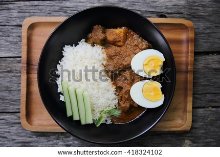 Curry rice on wood background - stock photo