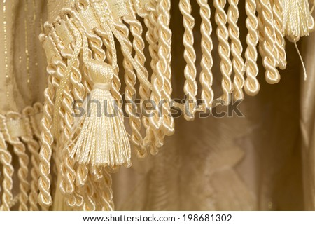 Curtain fragment with a fringe and tassels close-up, background - stock photo