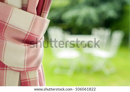 curtain with window looking into garden with table and chairs - stock photo