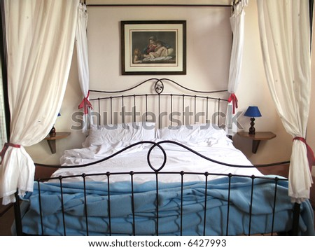 Curtained bed in Tuscan farmhouse - stock photo