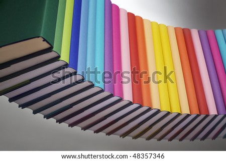 Curve alignment of in rainbow colors paper wrapped books with blank spine facing front, view from bottom-left, PHOTOGRAPH, NOT 3D RENDER. - stock photo