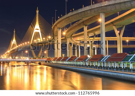 Curve of suspension bridge at riverside in twilight scene(Bangkok, Thailand) - stock photo