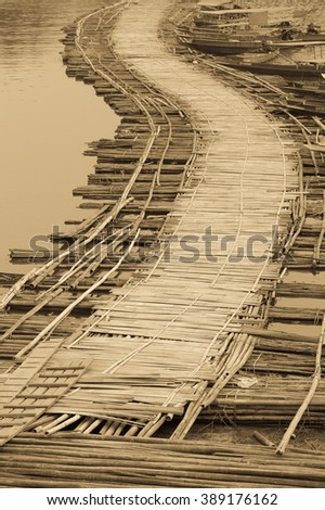 Curve of temporary bamboo bridge at Sangklaburi, Kanchanaburi in Thailand as sepia tone - stock photo