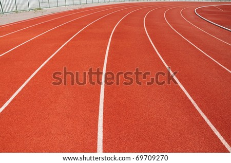 Curve on a red running track in arena - stock photo