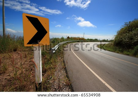 Curve road sign on down hill. - stock photo