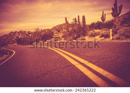 Curved Arizona Desert Road. Traveling Theme. Rocks and Cactuses Landscape. - stock photo