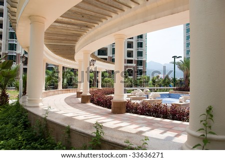 Curved corridor with a row of marble columns in a central garden - stock photo