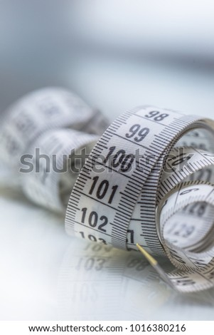 Curved measuring tape. Measuring tape of the tailor. Closeup view of white measuring tape.