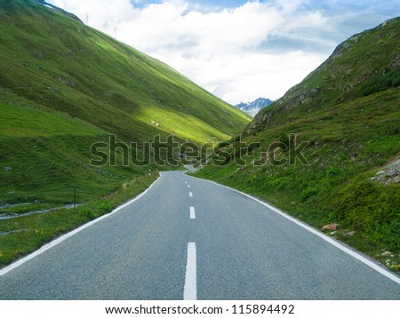 Curved narrow asphalt road in Switzerland Alps - stock photo