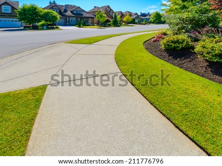 Curved pedestrian sidewalk in a nice neighborhood in the suburbs of Vancouver, Canada. - stock photo