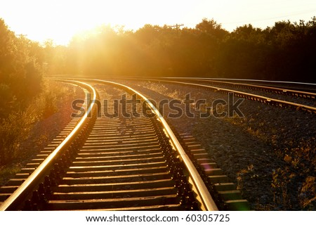 Curved railroad in sunset - stock photo