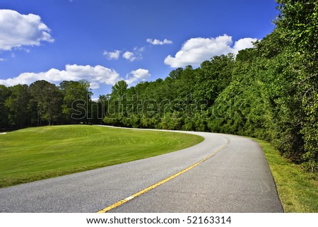 Curved road by green tree line and blue sky above - stock photo