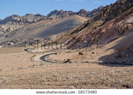 Curved road in Death Valley desert - stock photo