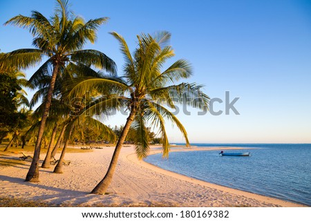 Curved seashore at dawn and moored boat on the blue sky background